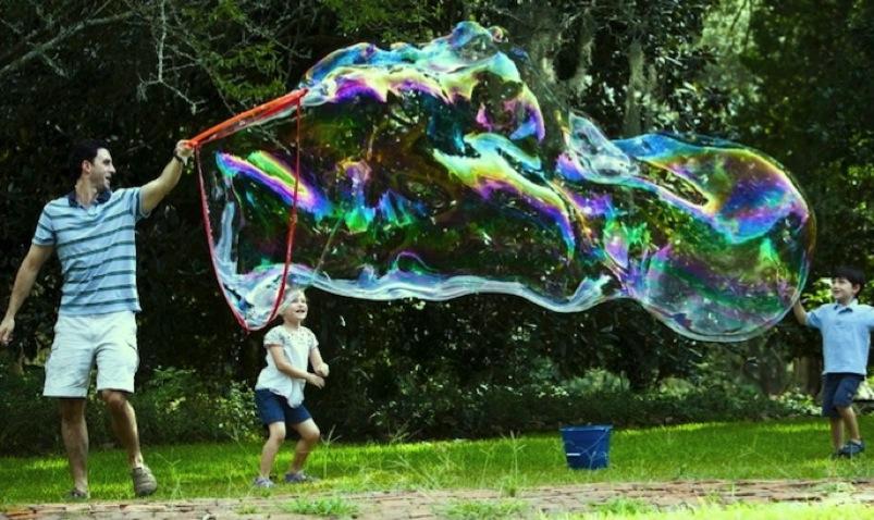 выдувание гиганских мыльных пузырей при попощи спец инструмента